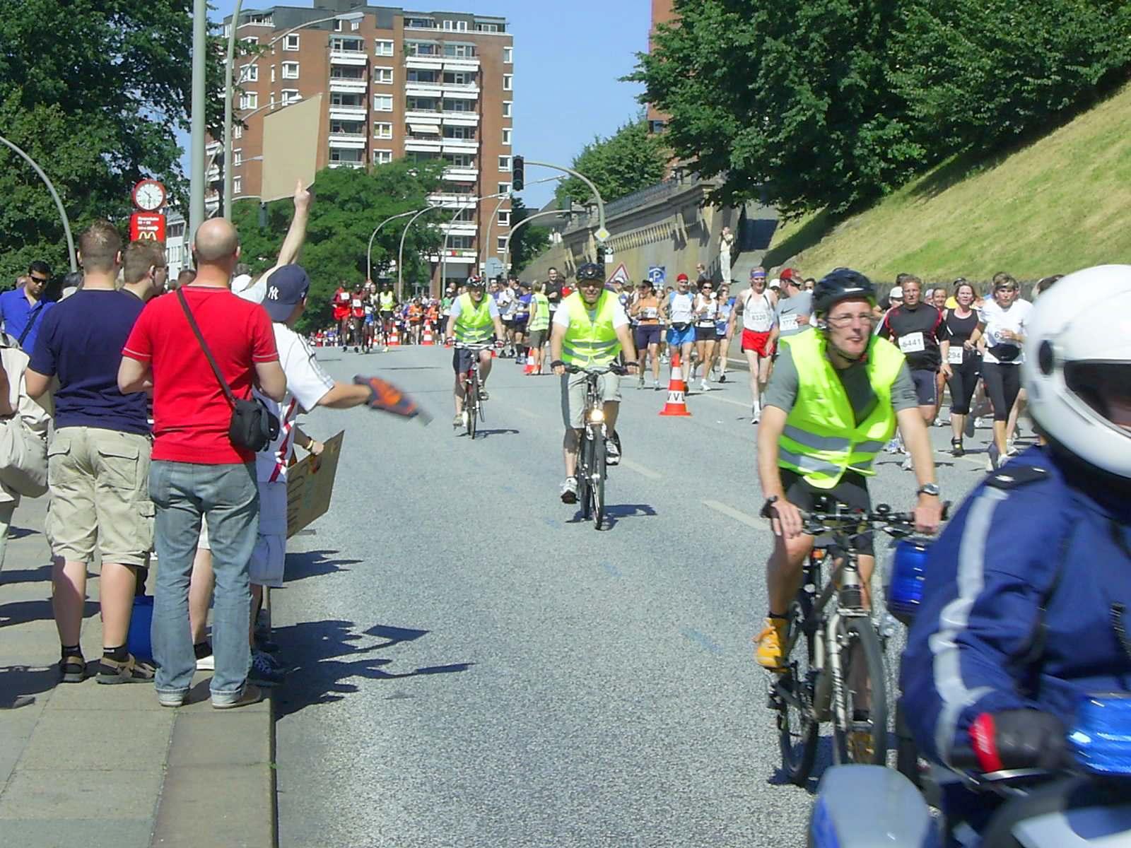 16. hella Halbmarathon 2010: Hinter dem Lautsprecherwagen kommen die Führungsfahrräder auf der Überholspur (links), kurz dahinter die Spitzenläufer. Rechts das breite Feld noch auf der 1. Runde...